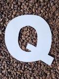 märka Q i vit och bakgrund med grillade kaffebönor, bakgrund och textur arkivfoto