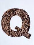 märka Q med grillade kaffebönor och vit bakgrund fotografering för bildbyråer