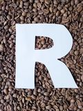 märka R i vit och bakgrund med grillade kaffebönor, bakgrund och textur royaltyfria foton