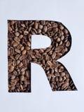 märka R med grillade kaffebönor och vit bakgrund arkivbilder