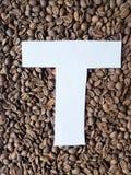 märka T i vit och bakgrund med grillade kaffebönor, bakgrund och textur royaltyfria foton