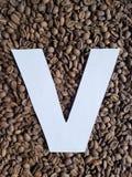 märka V i vit och bakgrund med grillade kaffebönor, bakgrund och textur arkivbilder