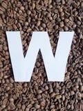 märka W i vit och bakgrund med grillade kaffebönor, bakgrund och textur royaltyfri foto