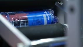 Märkande maskin på vattenproduktionslinjen Vattenprodukter som märker på mejerifabriken Slut upp emballagevattenflaskor lager videofilmer