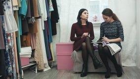Märkes- arbete för ung kvinna med den unga härliga kunden, portion som finner en klänning för ett parti lager videofilmer