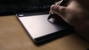 Märkes- arbete med diagramminnestavlan, händer av en man som arbetar med teckningsminnestavlan för en dator, den mjuka fokusen, s lager videofilmer