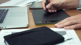 Märkes- arbete med diagramminnestavlan, händer av mannen som arbetar med teckningsminnestavlan lager videofilmer