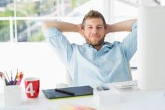 Märkes- koppla av på hans skrivbord som ler på kameran Royaltyfria Foton