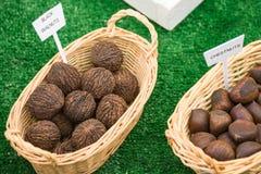 Märkta korgar av svarta valnötter och kastanjer royaltyfria foton