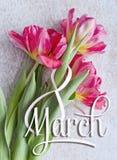 8. März Grußkarte der internationalen Frauen Tages Weiße Tabelle acht und ein Blumenstrauß von drei roten Tulpen Lizenzfreies Stockfoto