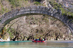 27. März 2011 Konitsa, Griechenland - flößend in Voidomatis-Fluss, Epirus, Griechenland, unter einer alten Steinbrücke Lizenzfreie Stockbilder