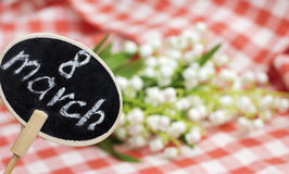 8. März Platte und Blumen auf unscharfem Hintergrund Lizenzfreie Stockbilder