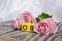 8. März Symbol und Rosen Zahl von acht auf Würfeln mit Rosen auf hölzernem Hintergrund Glückliches Frau ` s Tagesdesign Kann als  Stockbild