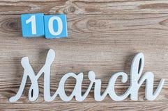 10. März Tag 10 des Marschmonats, Tagesübersicht auf Holztischhintergrund mit geschnitztem Text Frühlingszeit… Rosenblätter, natü Stockbilder