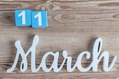 11. März Tag 11 des Marschmonats, Tagesübersicht auf Holztischhintergrund mit geschnitztem Text Frühlingszeit… Rosenblätter, natü Lizenzfreie Stockbilder
