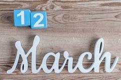 12. März Tag 12 des Marschmonats, Tagesübersicht auf Holztischhintergrund mit geschnitztem Text Frühlingszeit… Rosenblätter, natü Lizenzfreie Stockfotografie