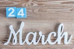 24. März Tag 24 des Marschmonats, Tagesübersicht auf Holztischhintergrund mit geschnitztem Text Frühlingszeit… Rosenblätter, natü Stockbilder