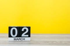 2. März Tag 2 des Monats, Kalender auf Tabelle mit gelbem Hintergrund Frühlingszeit, leerer Raum für Text Lizenzfreies Stockfoto