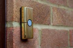 Mässing-färgad ringklocka på en tegelstenvägg Royaltyfri Fotografi