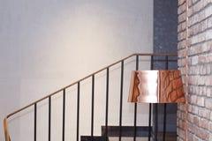 Mässingsgolvlampa bredvid en tegelstenvägg nära trappa royaltyfri bild