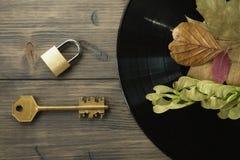 Mässingshänglås och tangent bredvid tappningvinylrekord fotografering för bildbyråer