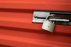 Mässingshänglås på orange metalldörr royaltyfria foton