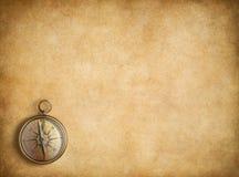 Mässingskompass på tom tappningpappersbakgrund Arkivfoto