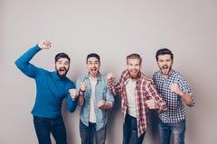 Mästare! Fyra förbluffade unga män är stå och göra en gest för arkivfoton