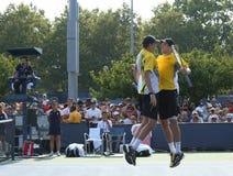 Mästare Mike och Bob Bryan som för den storslagna slamen firar seger efter första rundadubbletter, matchar på US Open 2013 Royaltyfri Foto