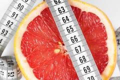 Mäta bandet med grapefrukten Arkivbilder