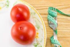 Mäta bandet och en gaffel med den isolerade tomaten Royaltyfria Foton