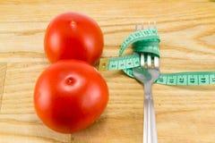 Mäta bandet och en gaffel med tomaten Arkivbild