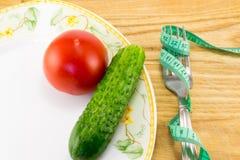 Mäta bandet och en gaffel med tomaten Arkivfoto