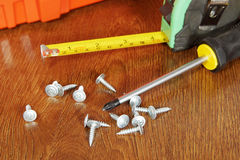 Mäta bandet och en skruvmejsel med skruvar på en trätabell Arkivbilder