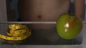 Mäta bandet och gräsplanäpplet i fett mans kylen, hälsa och kondition, detox stock video