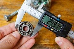 Mäta den yttre diametern av ett kullager med en elektronisk klämma Arkivbilder