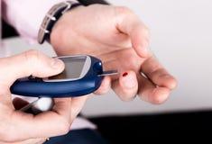 Mäta det jämna blodprovet för glukos genom att använda ultra mini- glucometer och liten droppe av blod från finger- och provremso Arkivfoton