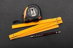 Mäta hjälpmedel och blyertspennan på svart arkivbild