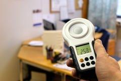 Mäta kontorsbelysning med luxmetern Arkivfoton