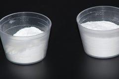 Mäta koppen med pulver arkivbild