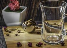 Mäta sked för te och kaffe med kaffebönor och torra teblad på en träplatta arkivfoto