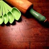Mäta skedar och den antika wood kavlen med det målade gröna handtaget Arkivfoton