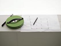 Mätande band, blyertspenna och byggnadsritning Arkivfoton