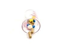 Mätglas med pills insida och yttersida Arkivbild
