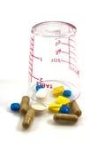 Mätglas med pills insida och yttersida Arkivfoto