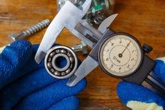 Mätning av den yttre diametern för kullager vid en förlage i handskar med en glidbanaklämma royaltyfri fotografi