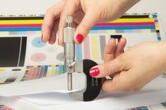 Mätning av tjocklek av en täcka av pappers- vid en mikrometer Royaltyfri Bild