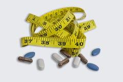Mätningsband med preventivpillerar, minnestavlor och kapseln Arkivbild