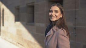 Młoda atrakcyjna kobieta cieszy się spacer w rodzimym mieście, ono uśmiecha się i machać, domowym zdjęcie wideo