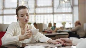 Młoda atrakcyjna kobieta jest pić kawowy i opowiadać z jej mężczyzną w restauracji podczas gdy trzymający jego rękę zdjęcie wideo